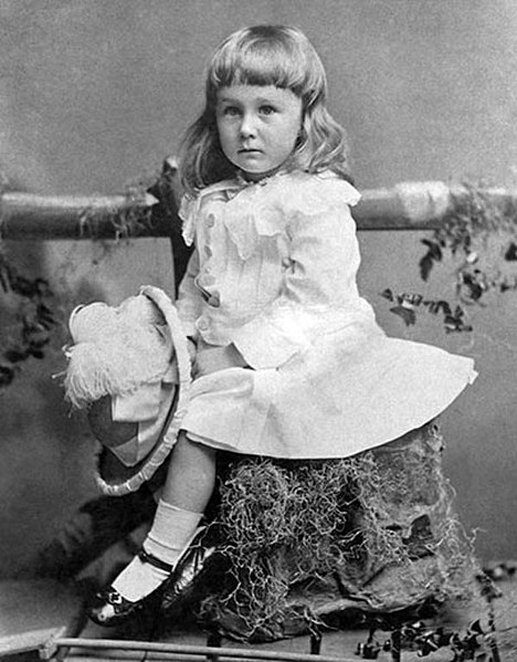 Two-and-a-half-year-old Franklin D. Roosevelt wearing a white dress and long hair.